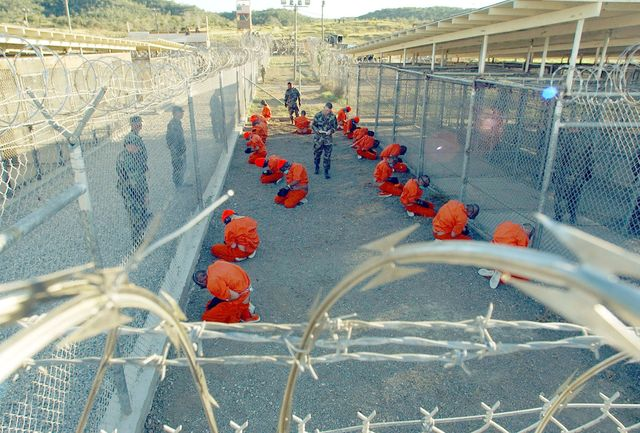 taliban prisoners in orange jumpsuits sitingt in holding area under the watchful eyes of military police at camp x ray at naval base guantanamo bay, cuba, during in processing to the temporary detention facility on jan 11, 2002 the detainees will be given a ba sic physical exam by a doctor, to include a chest x ray and blood samples drawn to assess their health    photo by shane mccoygreg mathiesonmaigetty images