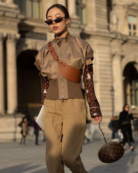一個穿咖啡色衣服的女生拿著飛碟包