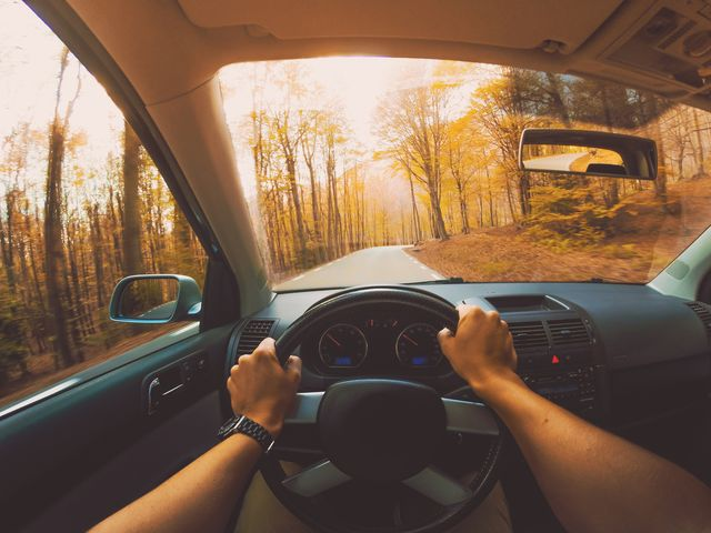 guy driving car from personal perspective in a beautiful mountain road between forest with autumn colors in the montseny nature reserve close to barcelona city during day trip