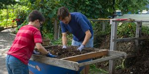 Guys Sifting Soil In Community Garden
