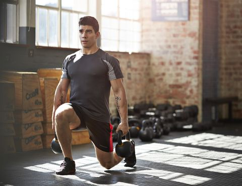 gym instructer doing lunges with kettlebells