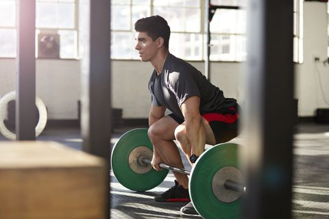 gym instructor lifting barbell at urban gym
