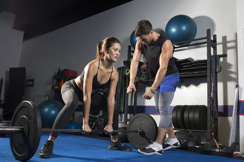 gym instructor teaching his student how to lift a barbell the right way