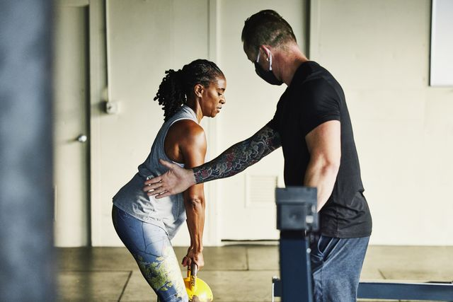 gym owner helping mature female client with technique during workout in gym