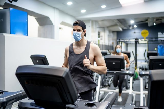 several young people running on treadmill in gym wearing face mask