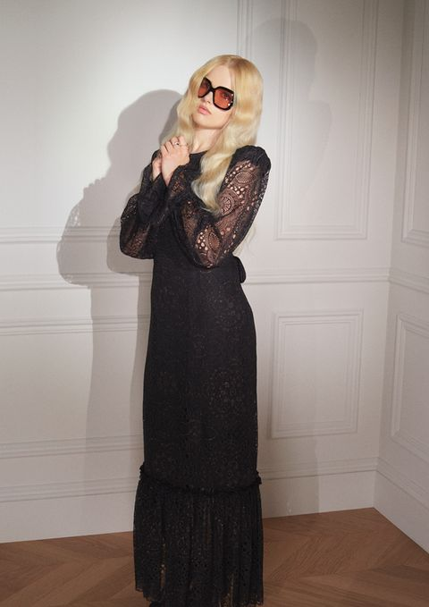 model wearing a long lace maxi dress with ruffled hem and bow tie back, wearing with black square sunglasses