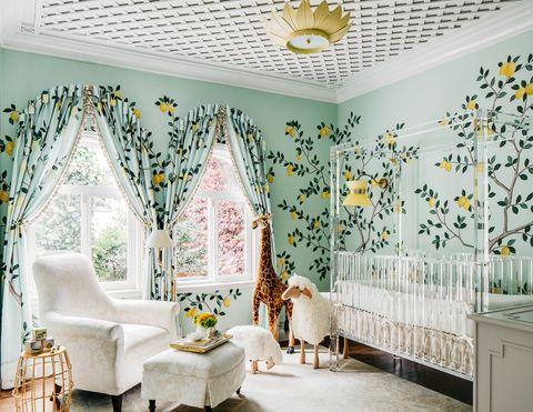 Habitación de bebé con cuna de metacrilato, rincón de lectura y papel pintado con limoneros