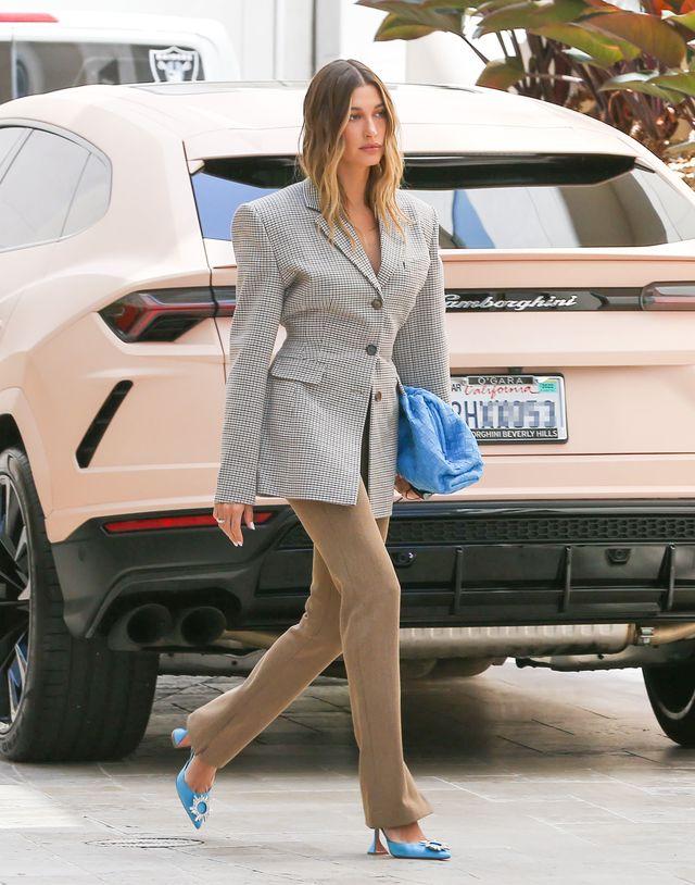 hailey bieber con americana con hombreras xl, pantalones beis, bolso de bottega veneta azul y salones azules de amina muaddi