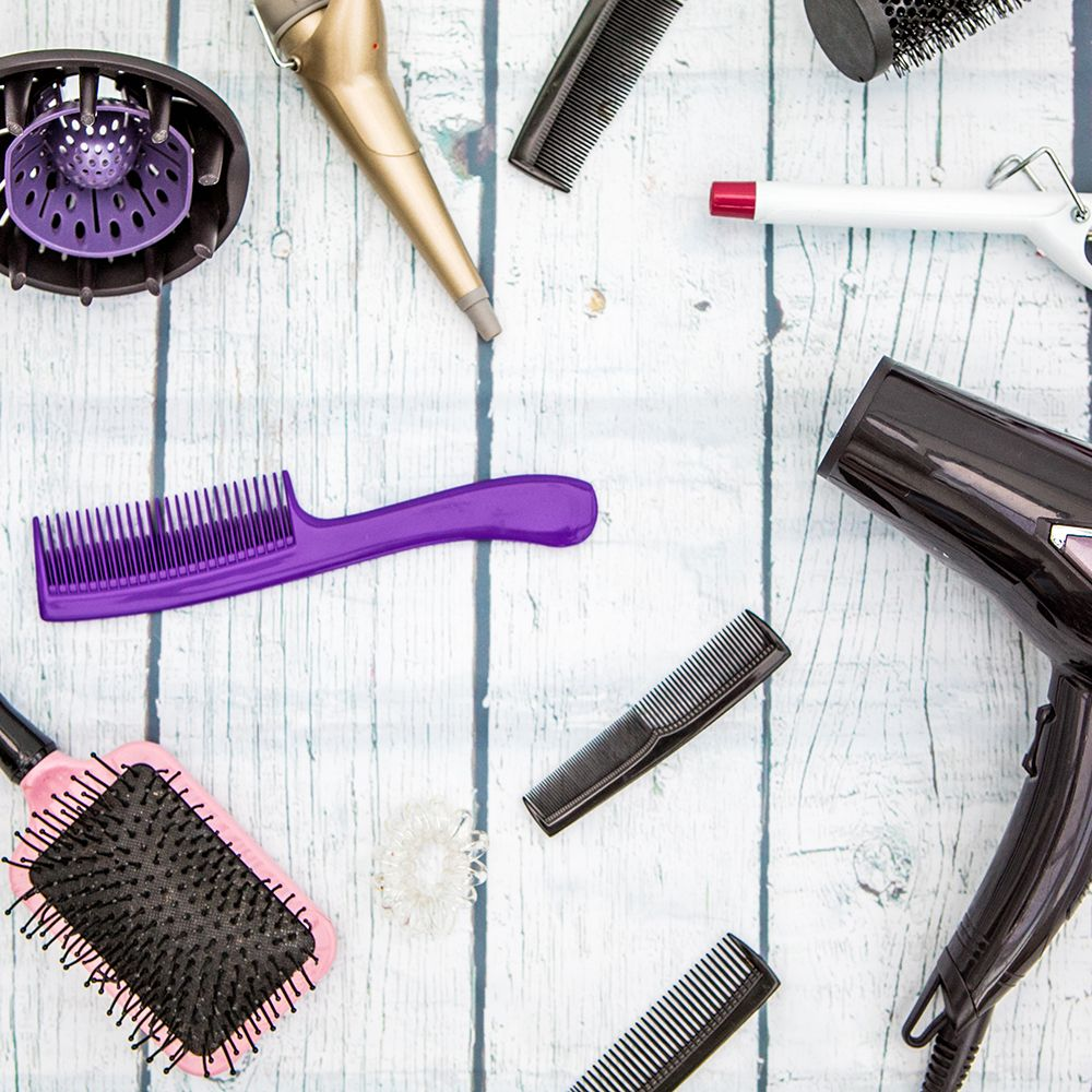 Various hair styling devices on white background, top view