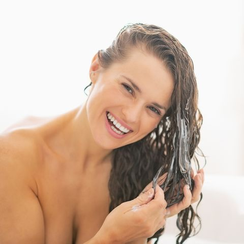 smiling young woman applying hair conditioner