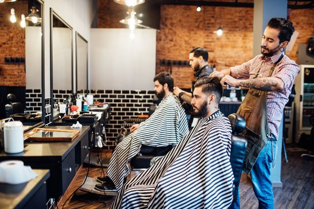 hairdressers cutting hair of clients in salon