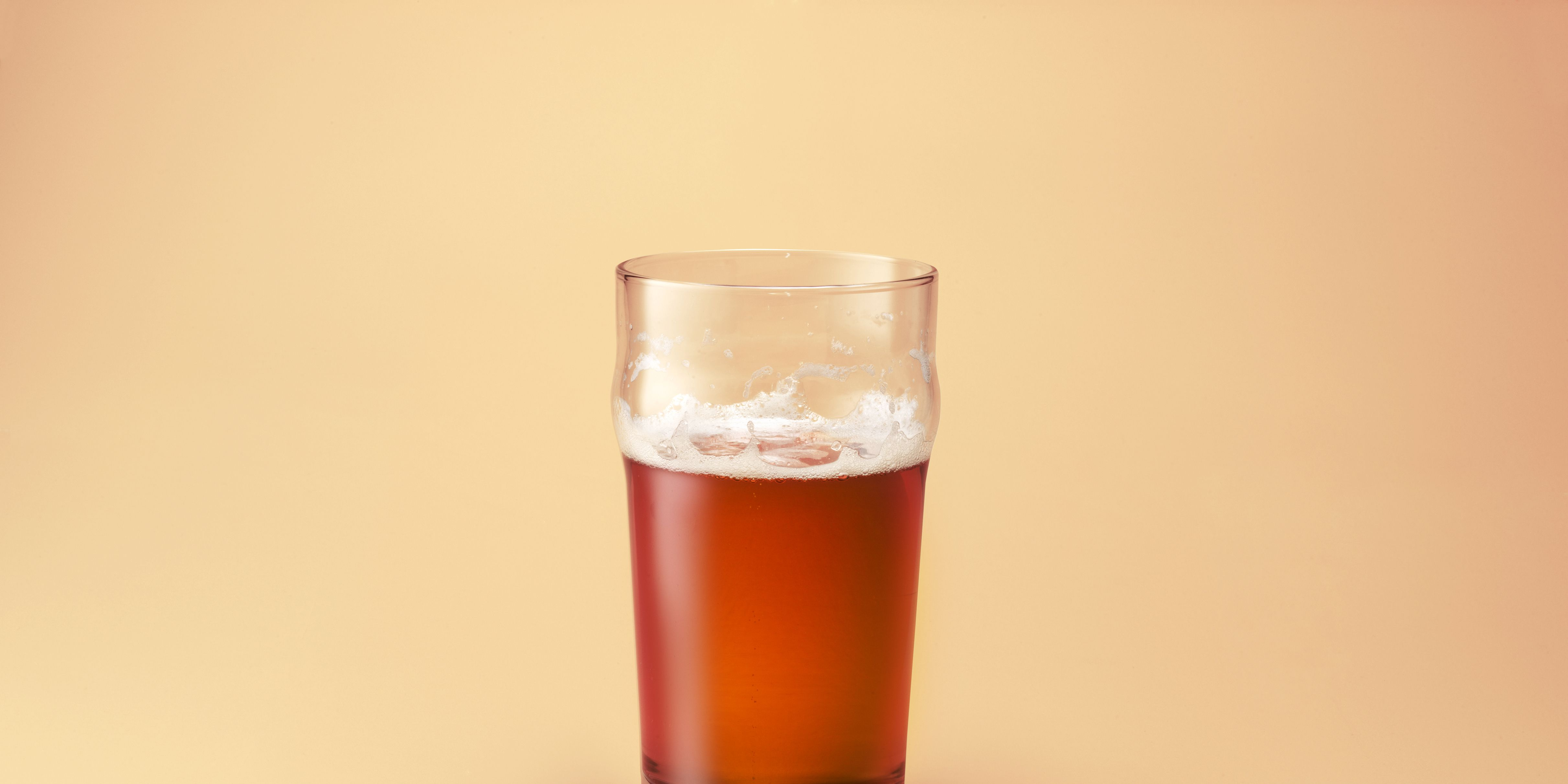 A half drunk pint of beer on a cream background