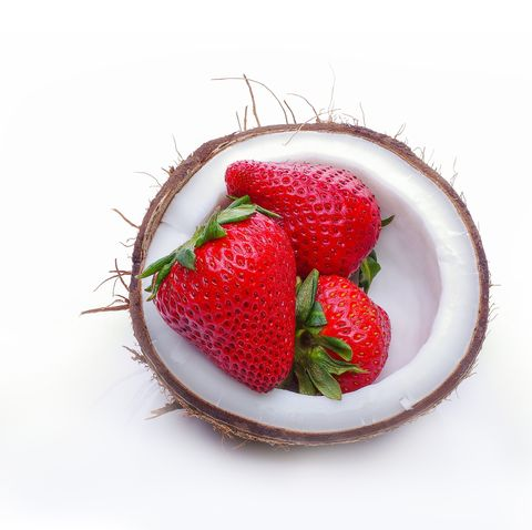 half of fresh coconut with strawberry on a white background coconut bowl with red berries inside, healthy, vegan, food, fashion, tropical concept with a copy space