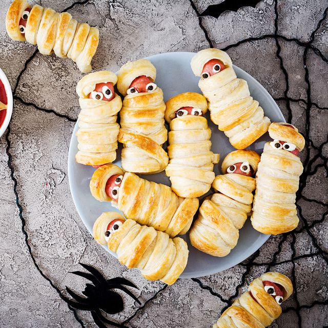 scary sausage mummies in dough with funny eyes on table funny decoration halloween food top view flat lay