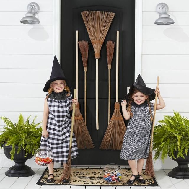 two girls dressed as witches with brooms