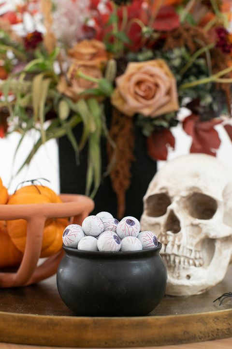 halloween candy set up with googly eye chocolates in cauldron bowl