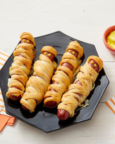 mummy hot dogs on black plate with mustard