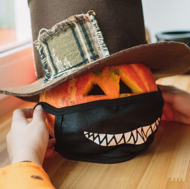kid putting halloween face mask on pumpkin