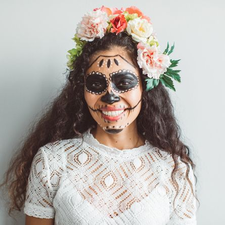 portrait of young woman with sugar skull creative make up for halloween