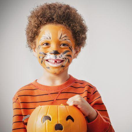 mixed race boy with tiger costume and halloween jackolantern bucket