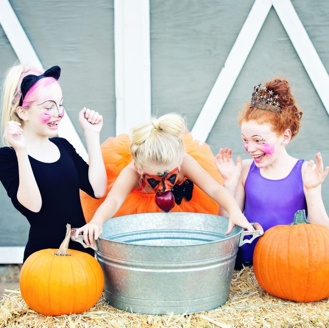 girls laughing and excited bobbing for apples at a halloween party