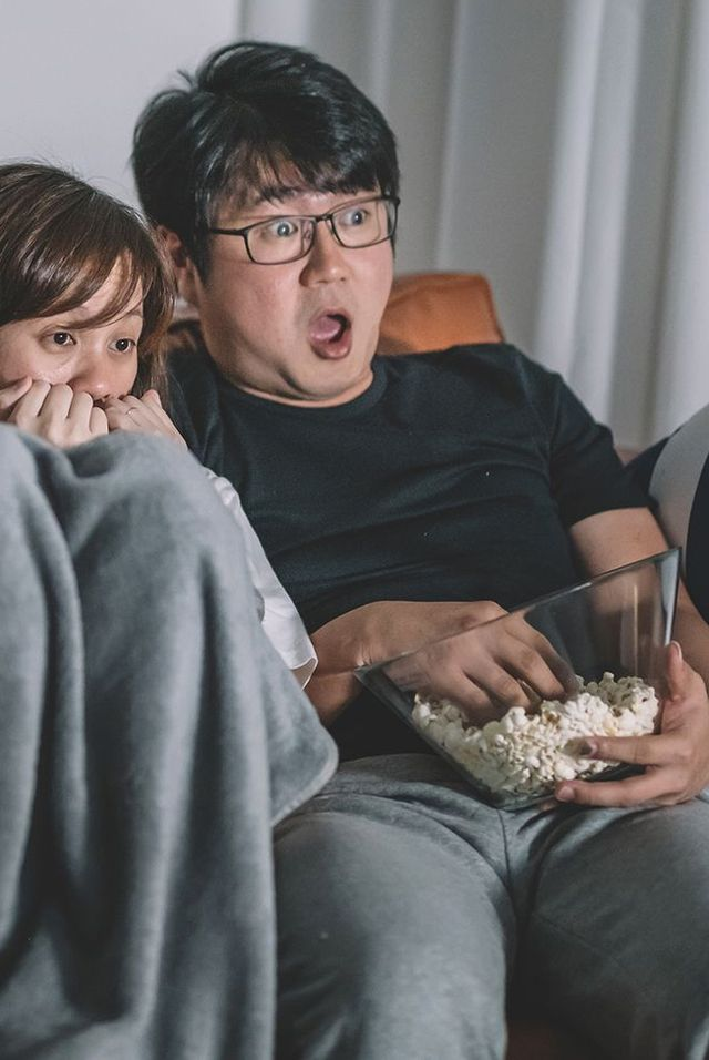 couple on couch with popcorn watching scary movie