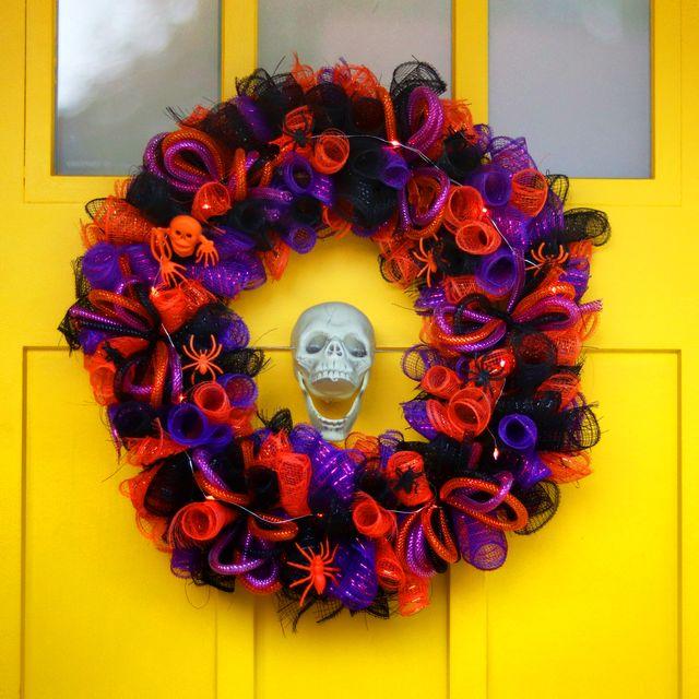 orange black and purple halloween wreath hanging on yellow door with skeleton
