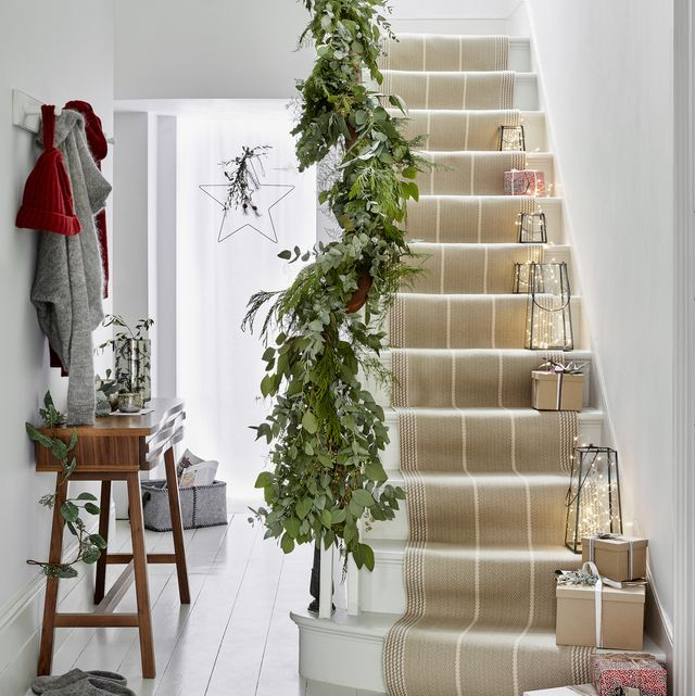 hallway, white wooden floors and stairway with fairy light filled lanterns runing up the stairs, green foliage along the banister
