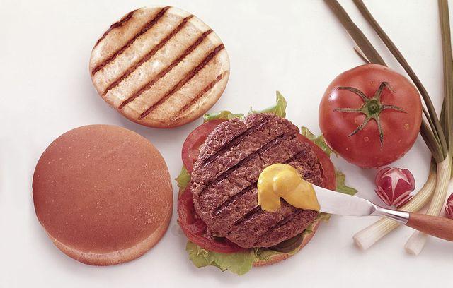 una persona se sirve una hamburguesa con mostaza y tomate