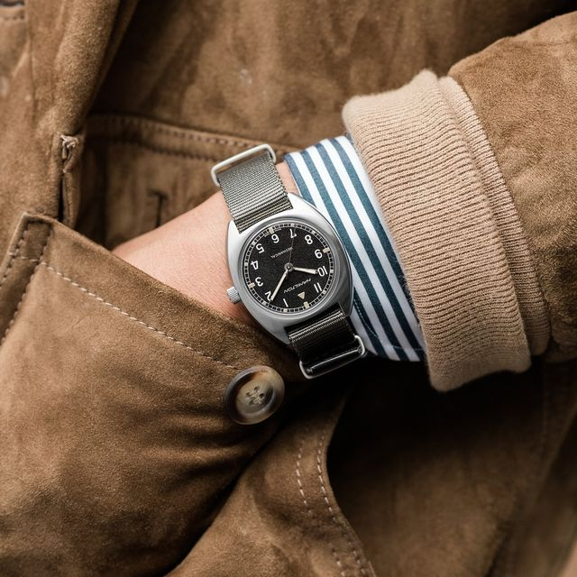 vintage style watch on wrist with leather coat