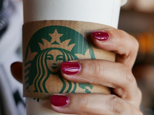 hand holding a coffee cup in a starbucks coffee shop  in