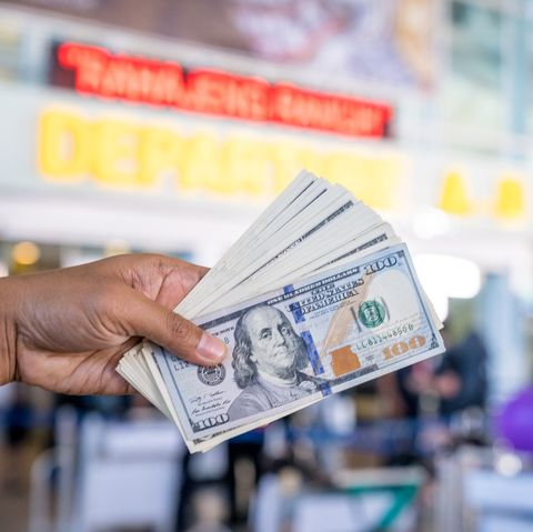 hand holding banknote at domestic departure in the international airport