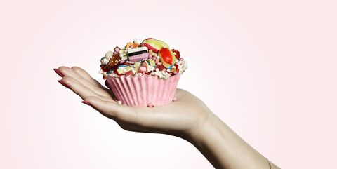 hand holding pink designed cupcake full of sweets