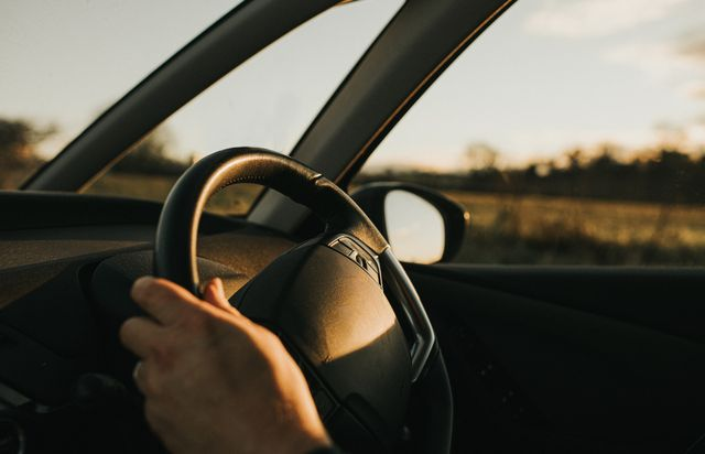 hand holding steering wheel in a car