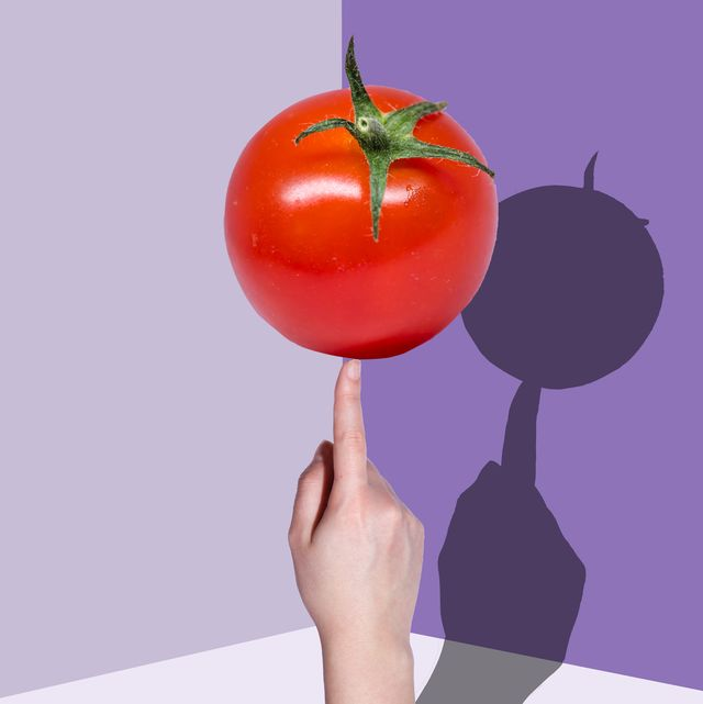 hand holding tomato with a shadow