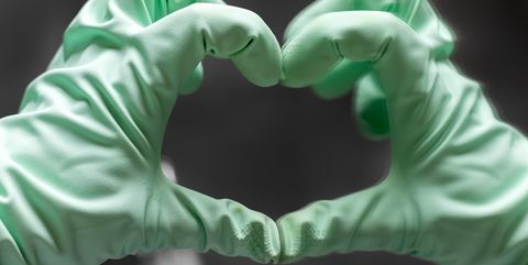 A hand in a mint green rubber glove shows a heart sign with its reflection in the mirror against a gray blurred background. Selective focus. Closeup view
