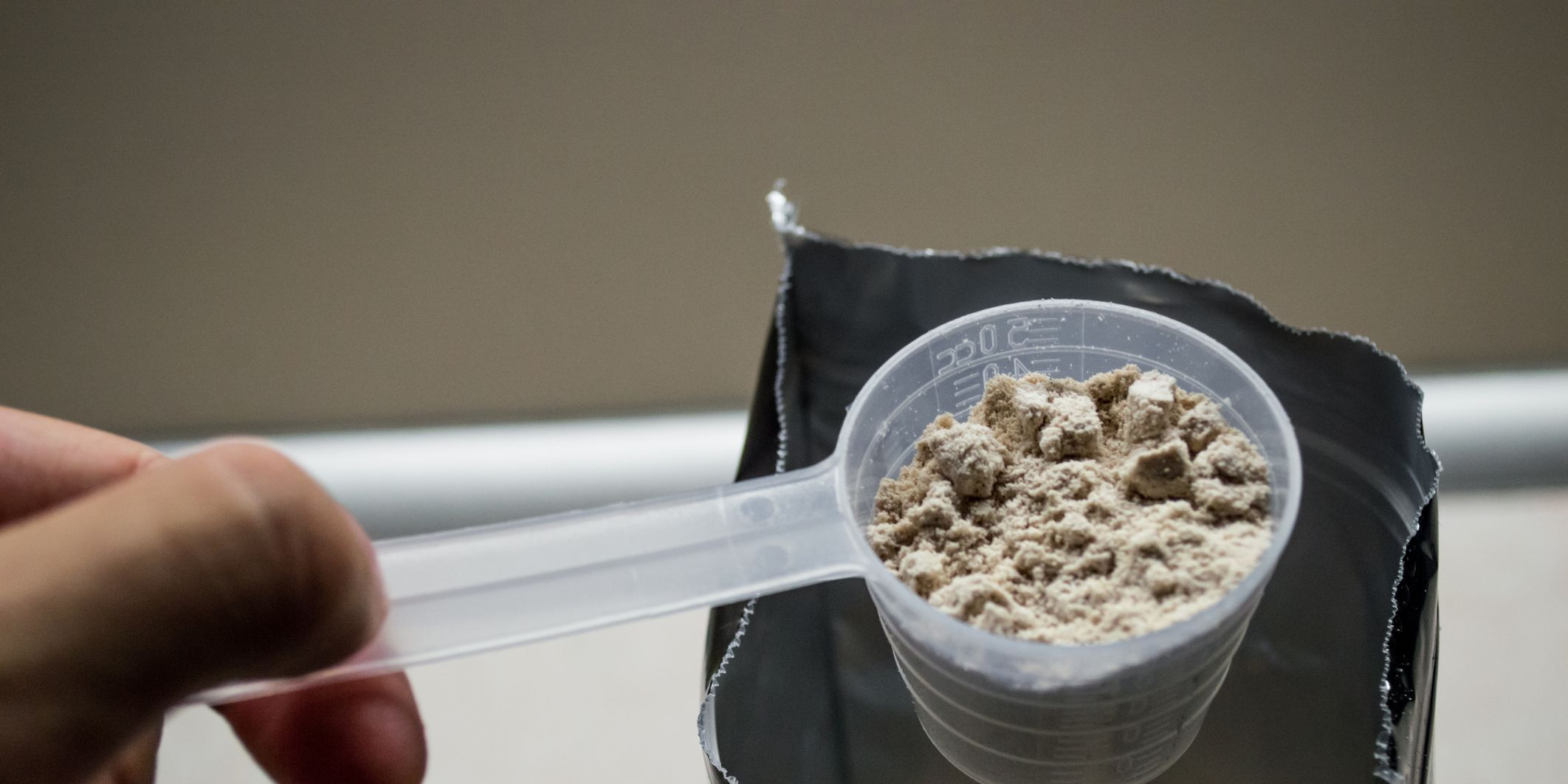 Hand Measuring Whey in a Bag of Whey Protein Powder
