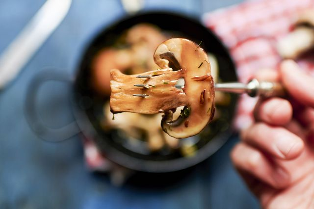 hand of man holding fork with single cooked mushroom