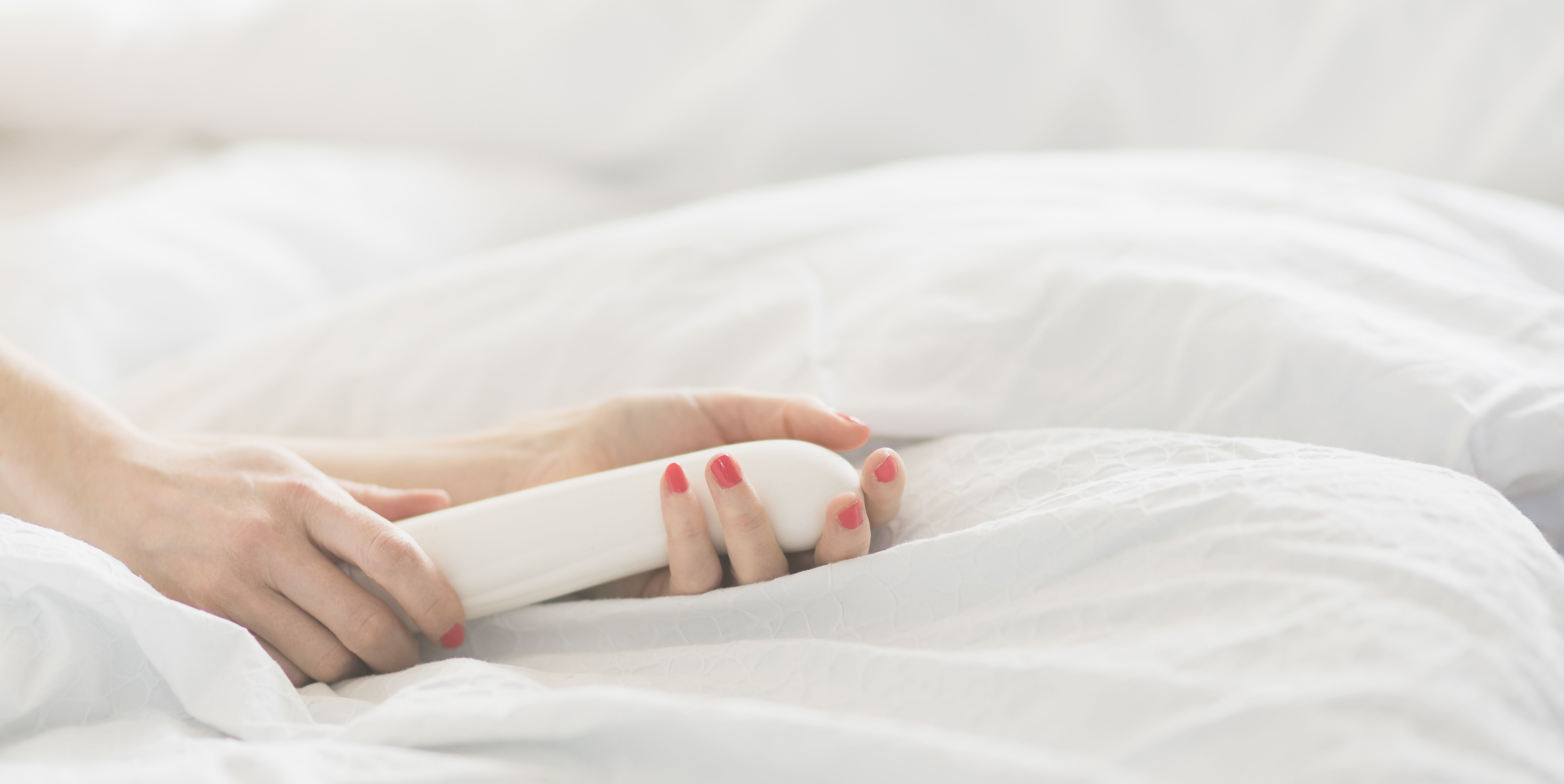 Hand of woman holding sex toy in bed
