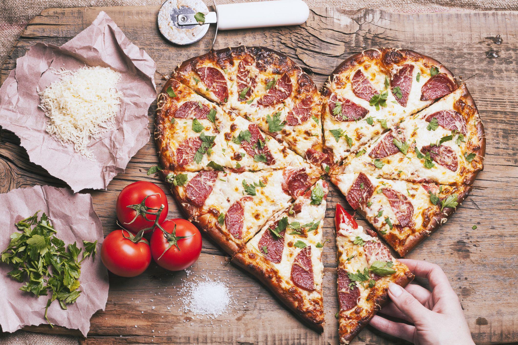 Main tirant une tranche de pizza en forme de coeur près des ingrédients sur une planche à découper