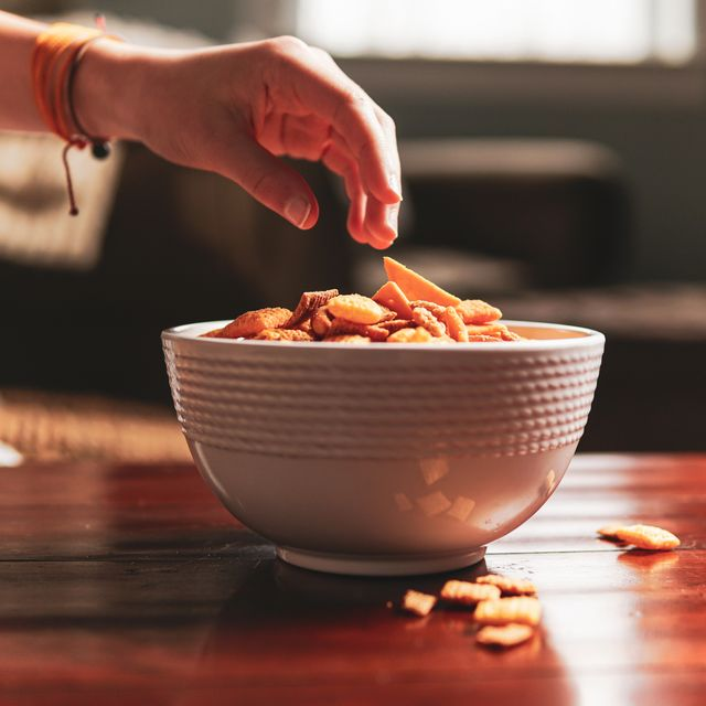 hand reaching for bowl of junk food snacks   flat lay copy space