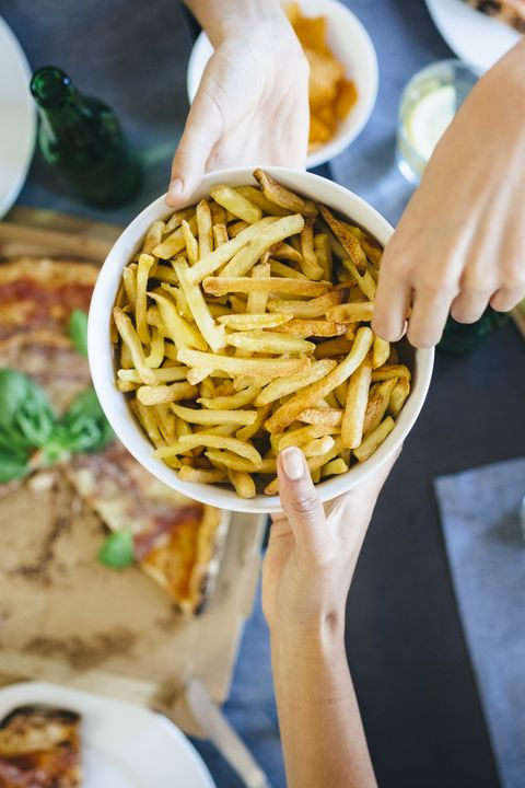 Hand taking French fries from bowl