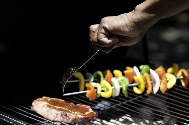 hand turning food on a grill