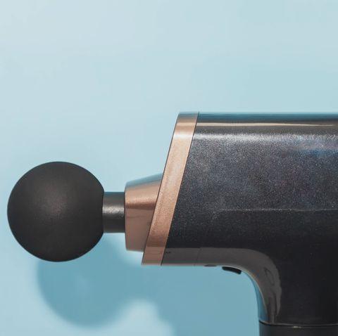 handheld wireless professional therapeutic shock massage gun on blue background