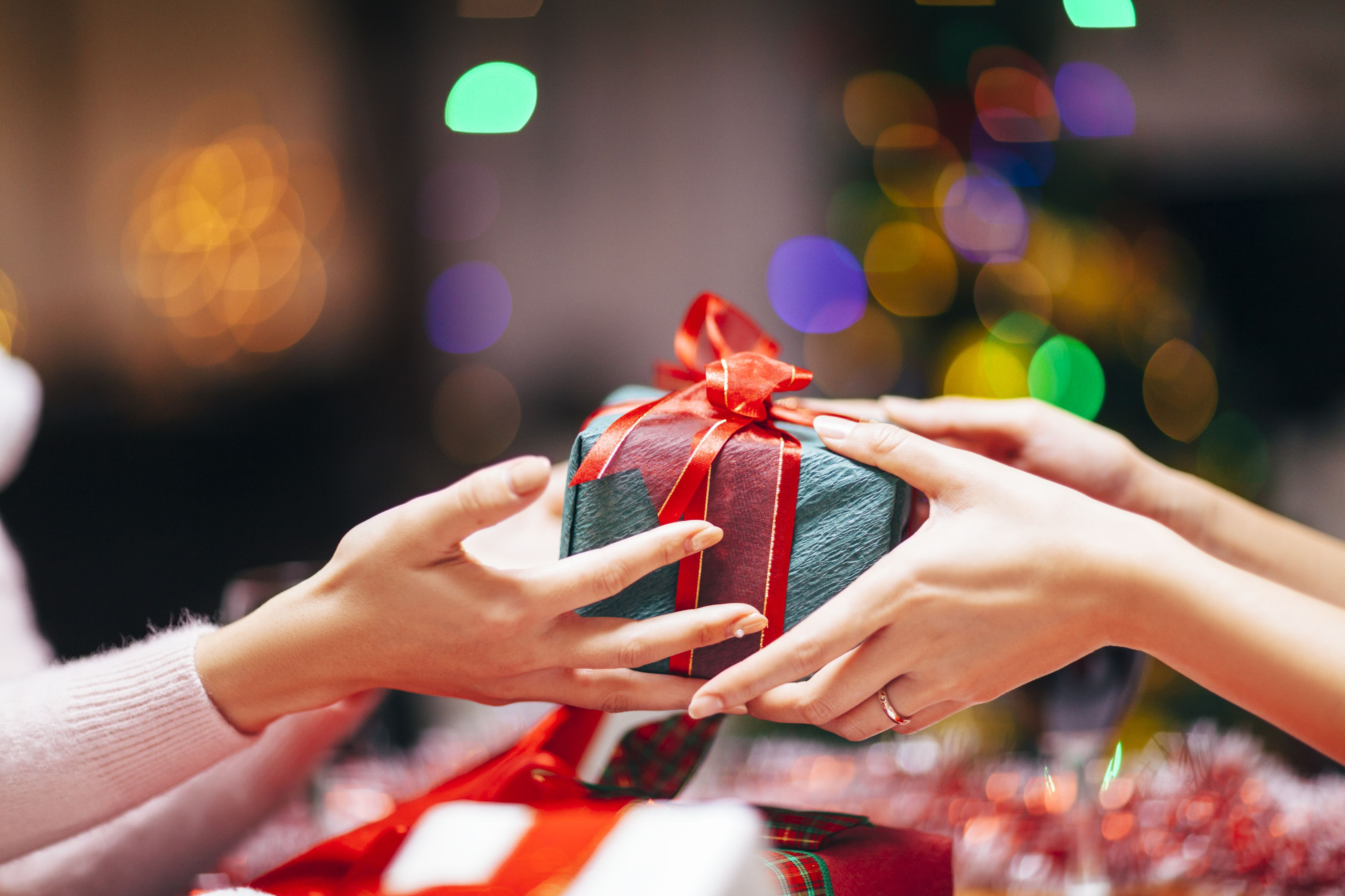 Hands Giving Gift Close-up & 20 Best White Elephant Gifts For 2018 - Presents For $20 Or Less