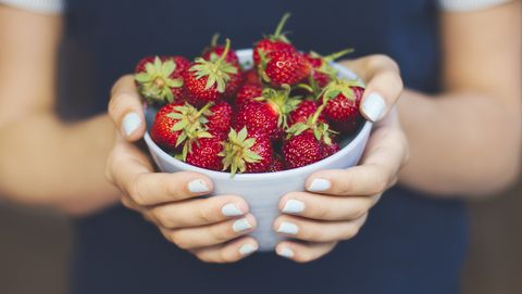 Hands holding bowl of strawberries