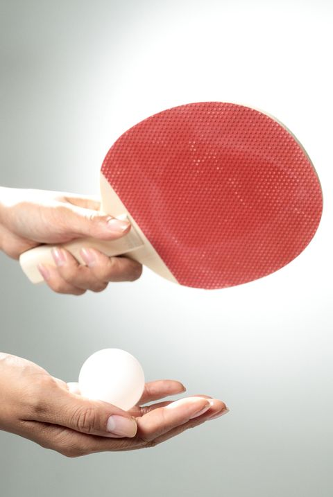 Hands holding table tennis paddle and ball