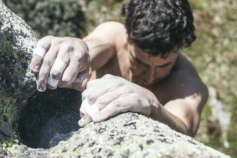Hands of a climber with sticking plaster and chalk during a boulder climbing