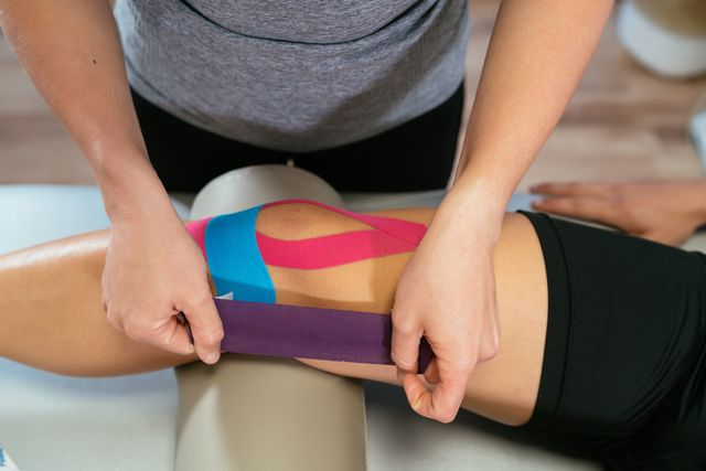 hands of a female physiotherapist taping light blue medical tape over another pink tape on a patient's knee