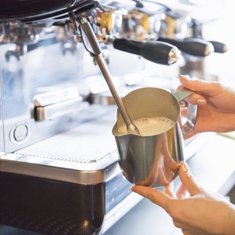 hands of female barista frothing milk with espresso machine in coffee shop